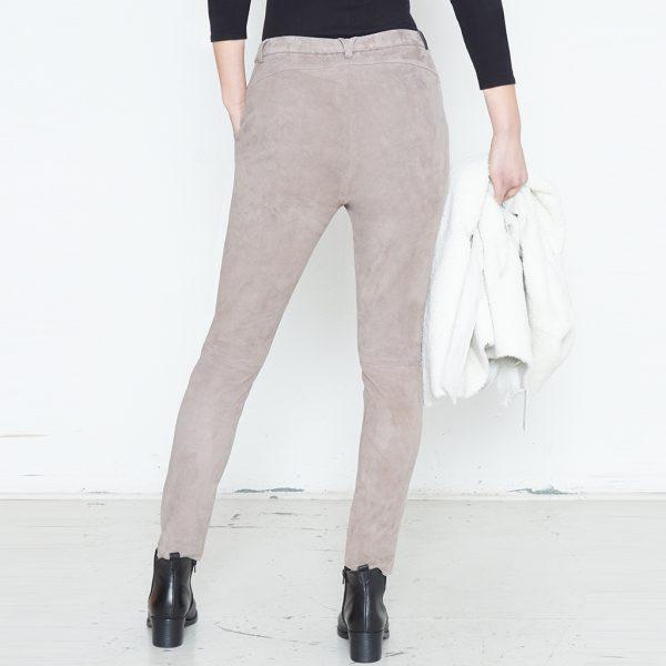 Beine von Frau in grauer Velour Lederhose von hinten